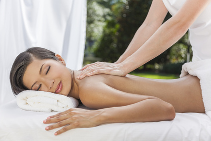 An Asian Chinese woman relaxing outside at a health spa while having a massage treatment